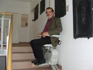 W. Brücher auf dem Treppenlift sitzend