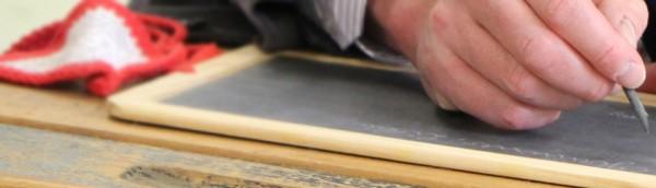 Mit dem Griffel wird auf der Schultafel Sütterlinschrift geübt.