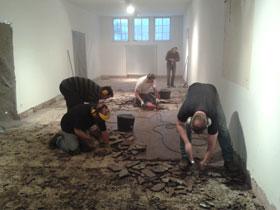 5 Männer stemmen die alten Bodenfließen in einem ansonsten leeren Raum ab.