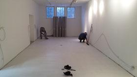Zwei Männer in einem ansonsten leeren Raum arbeiten an den Fußleisten.